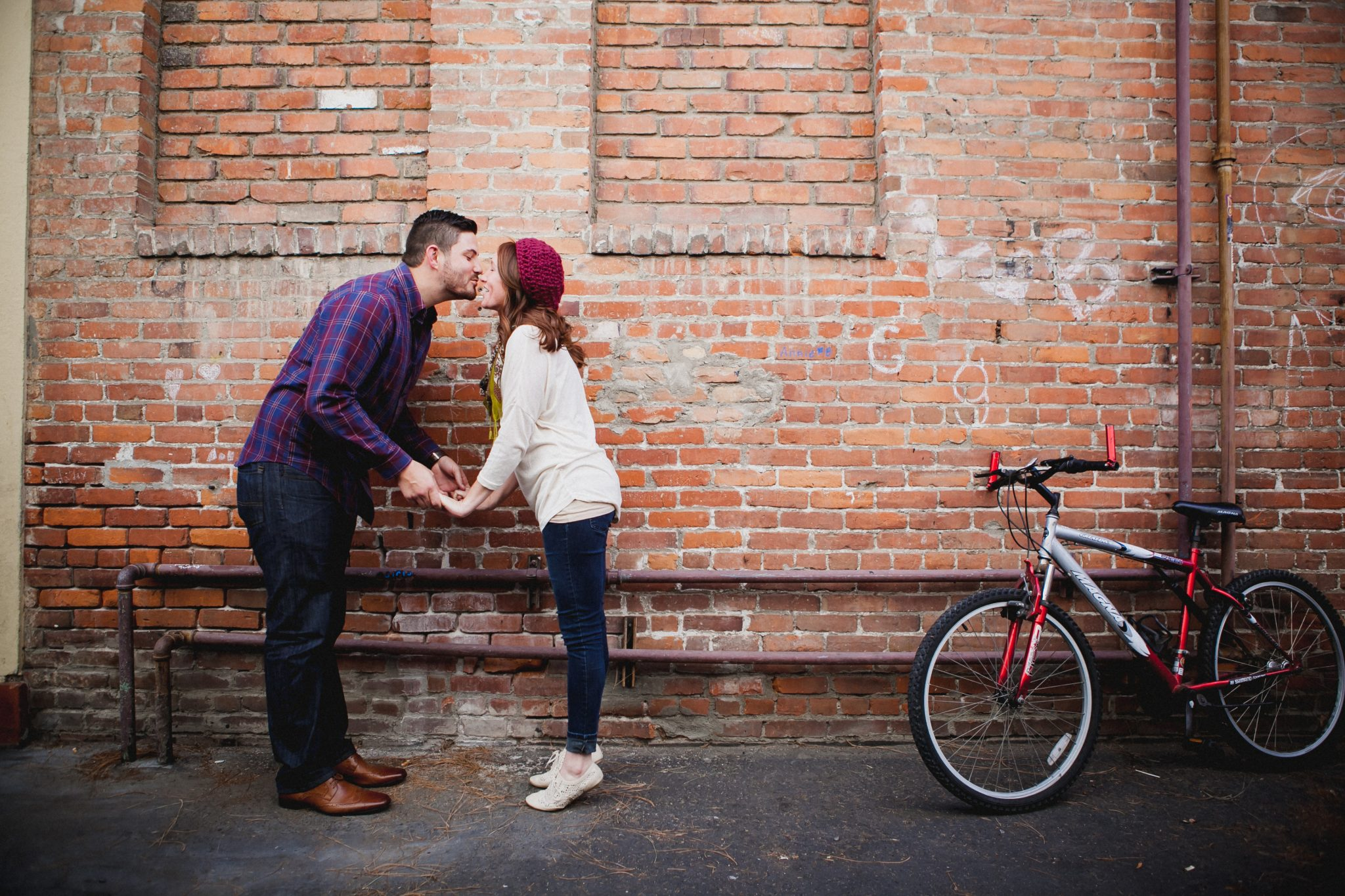 Couple kissing in front of a brick wall
