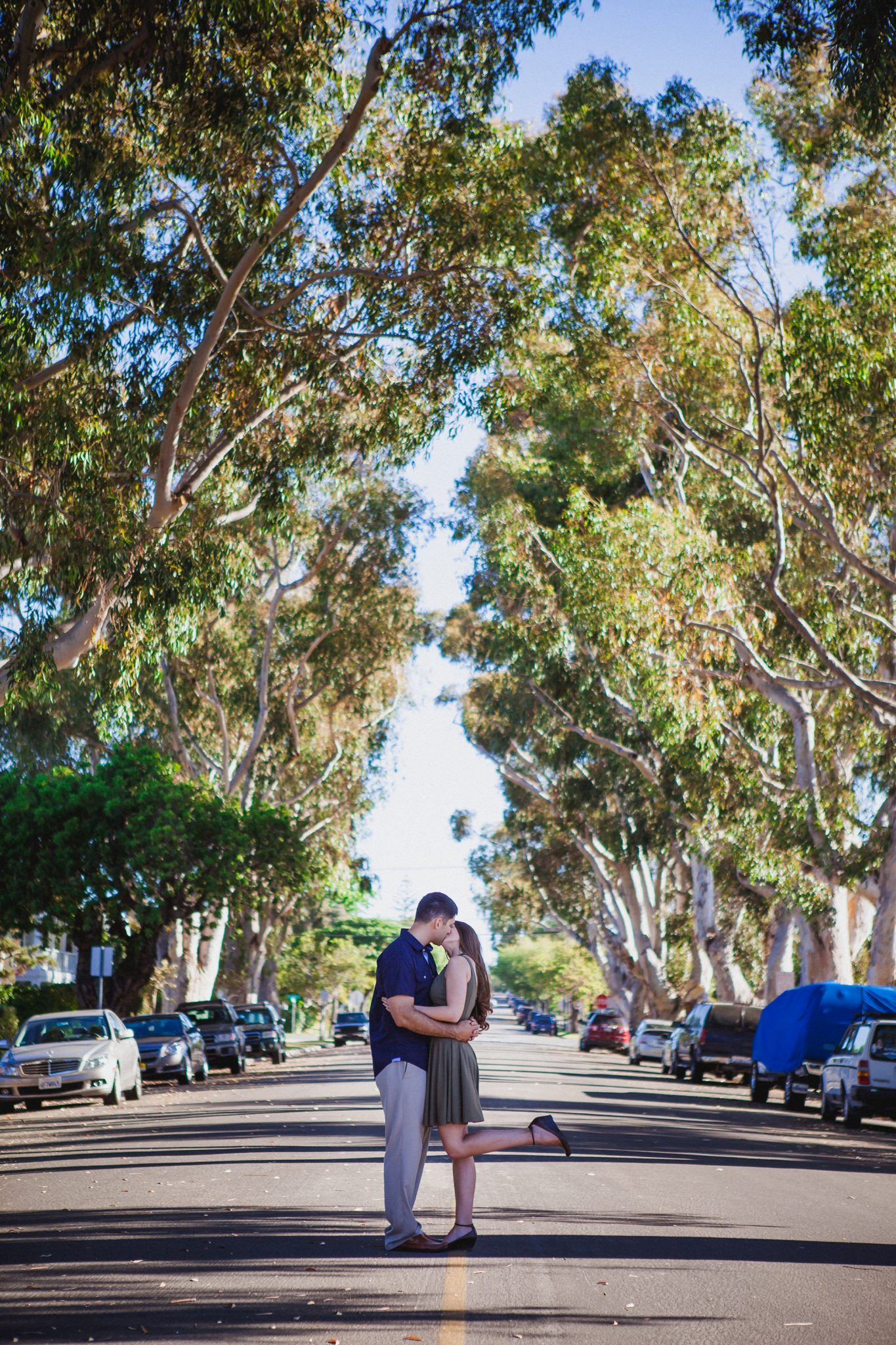 Engagement photo in a tree-lined street in Coronado