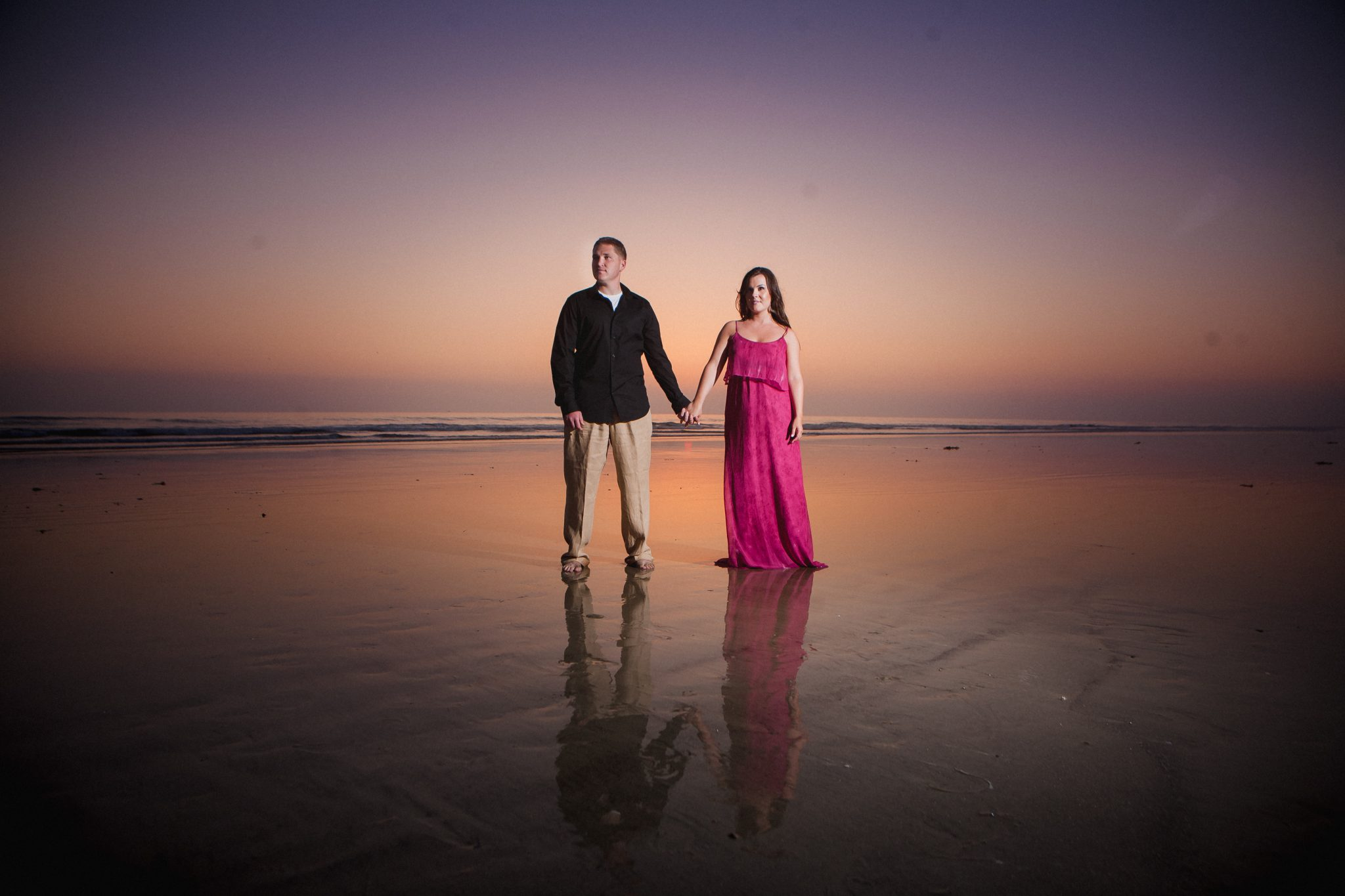 Couple standing by the ocean for their engagement shoot