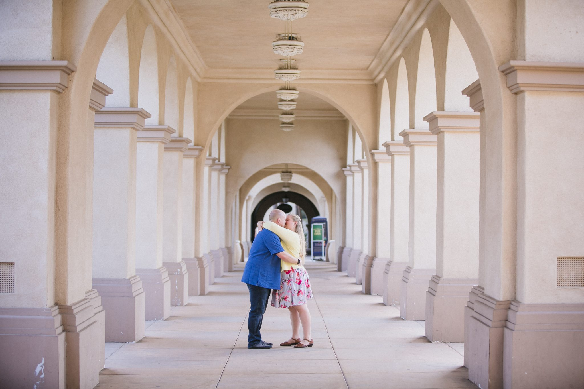 Couple kissing under the archways in Balboa Park