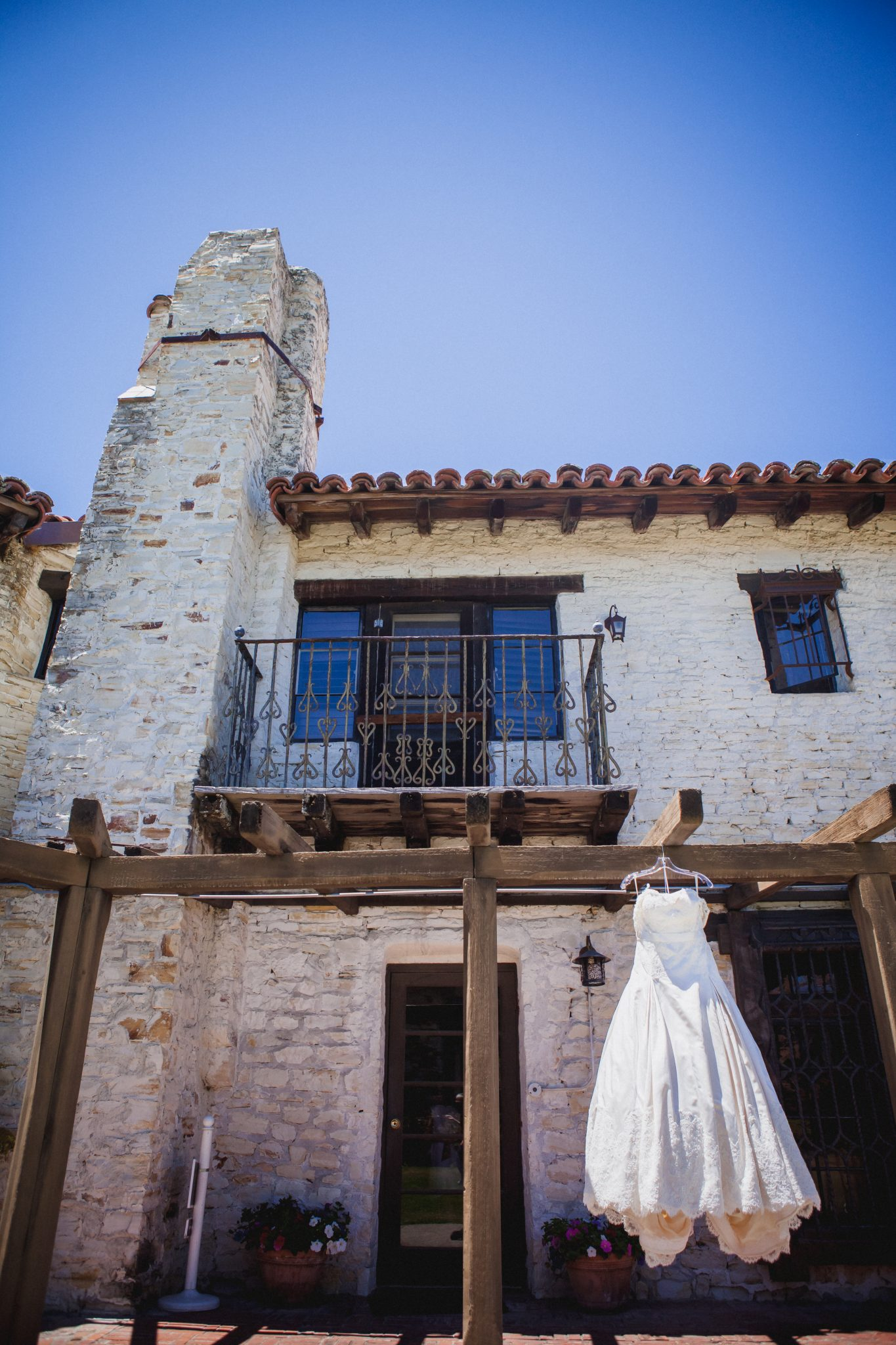 Wedding dress hanging from a rustic brick building