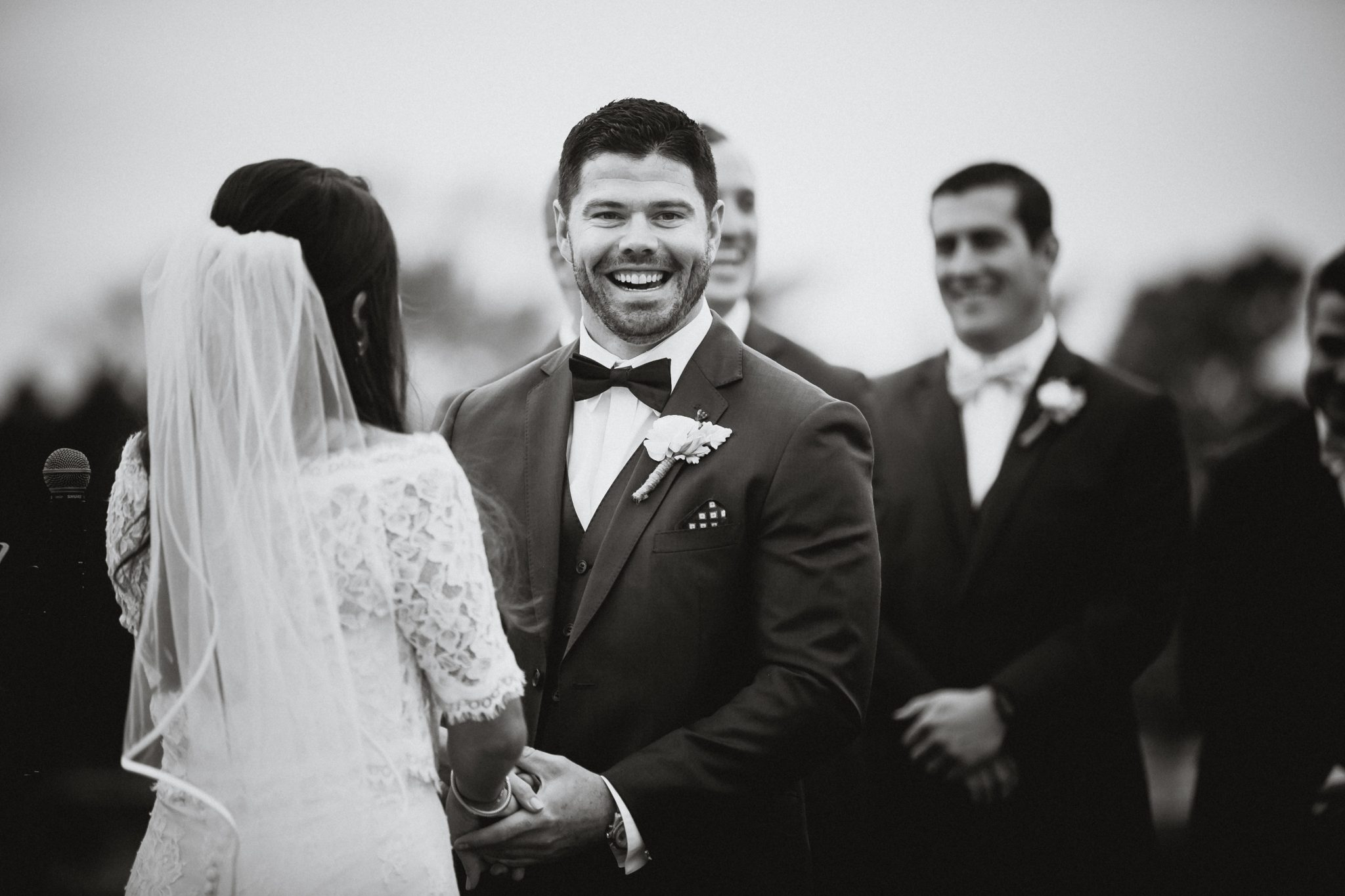 Black and white photo of the groom smiling during the ceremony