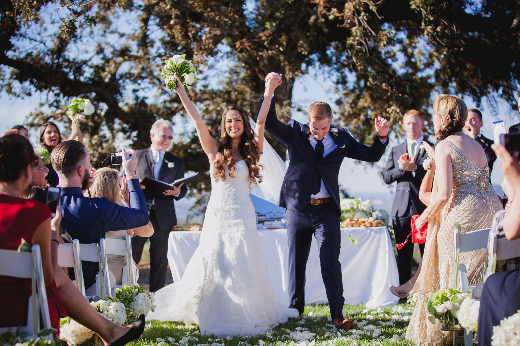 End of the wedding ceremony and the couple puts their hands in the air