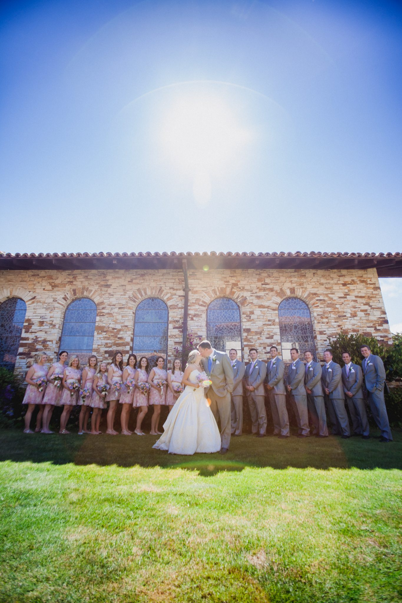 Wedding party portrait with a sunflare in front of the church