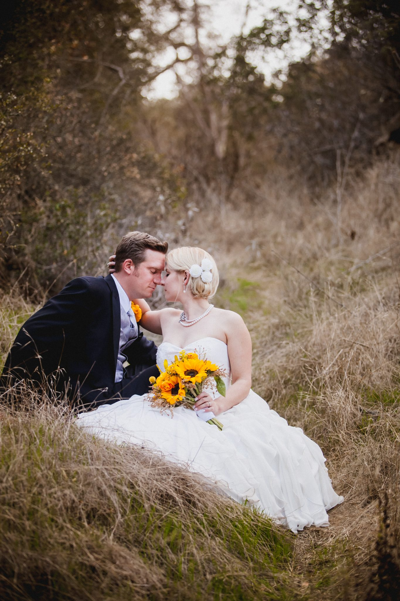 Intimate portrait of the couple sitting in a field