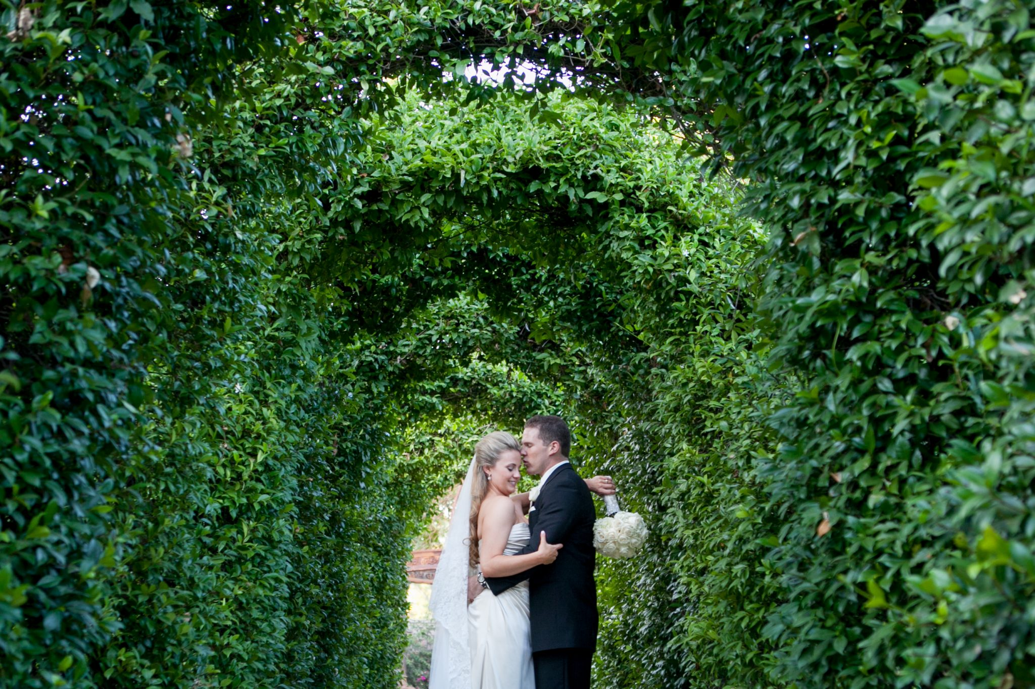 Bride and groom kissing under ivy archways