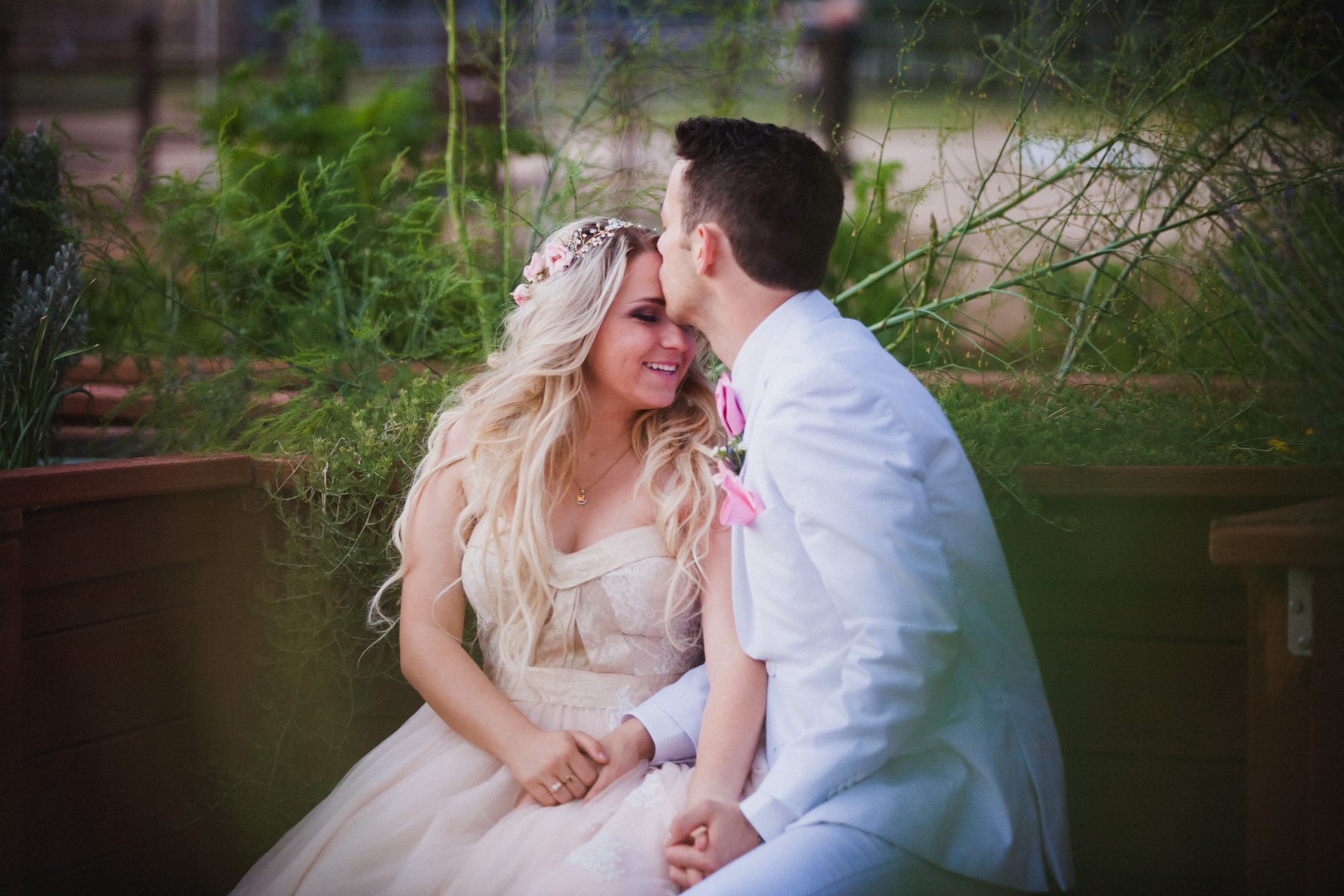 Groom in white kisses his bride's forehead