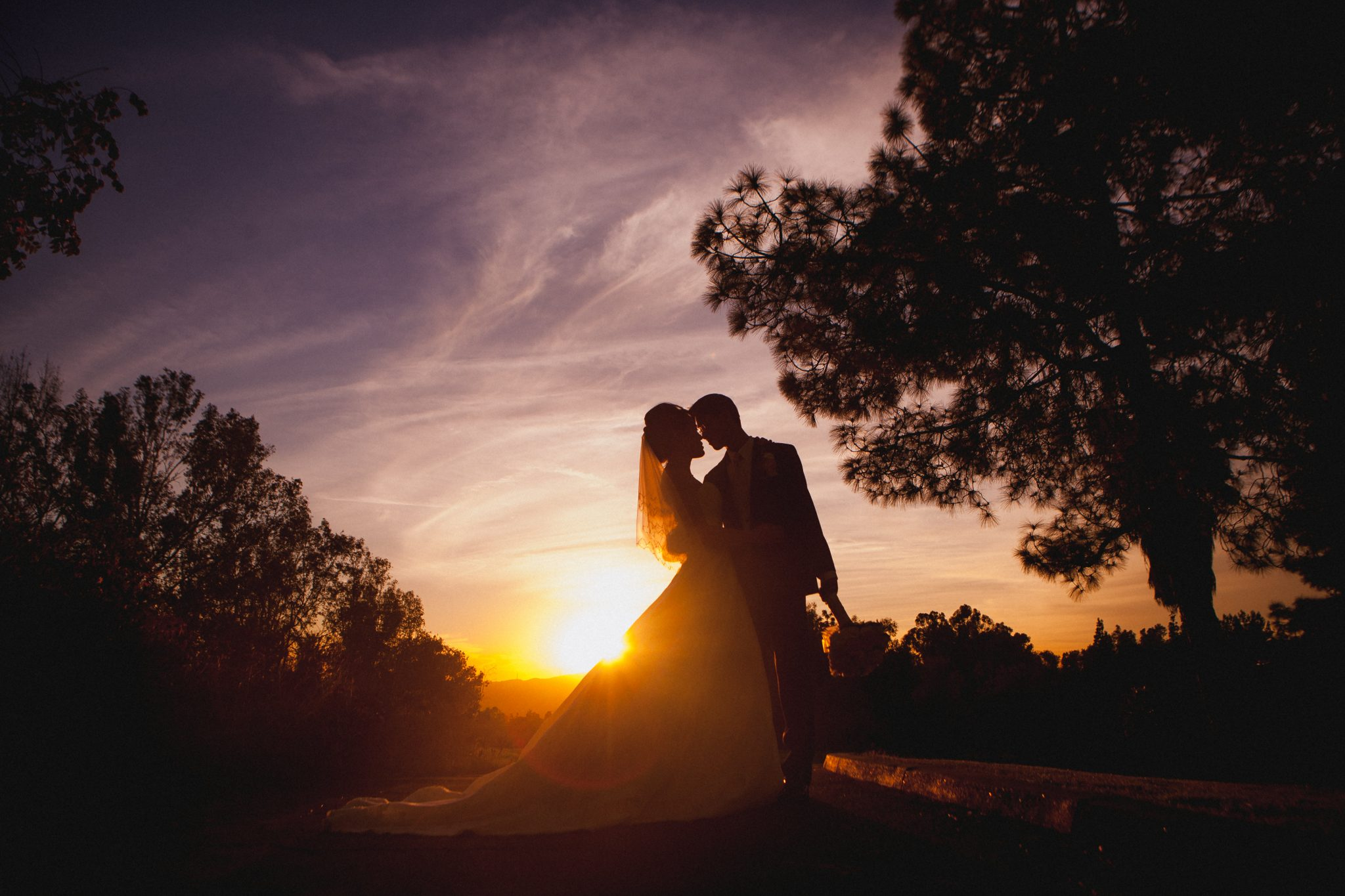 Silhouette of a bride and groom with colorful sunset
