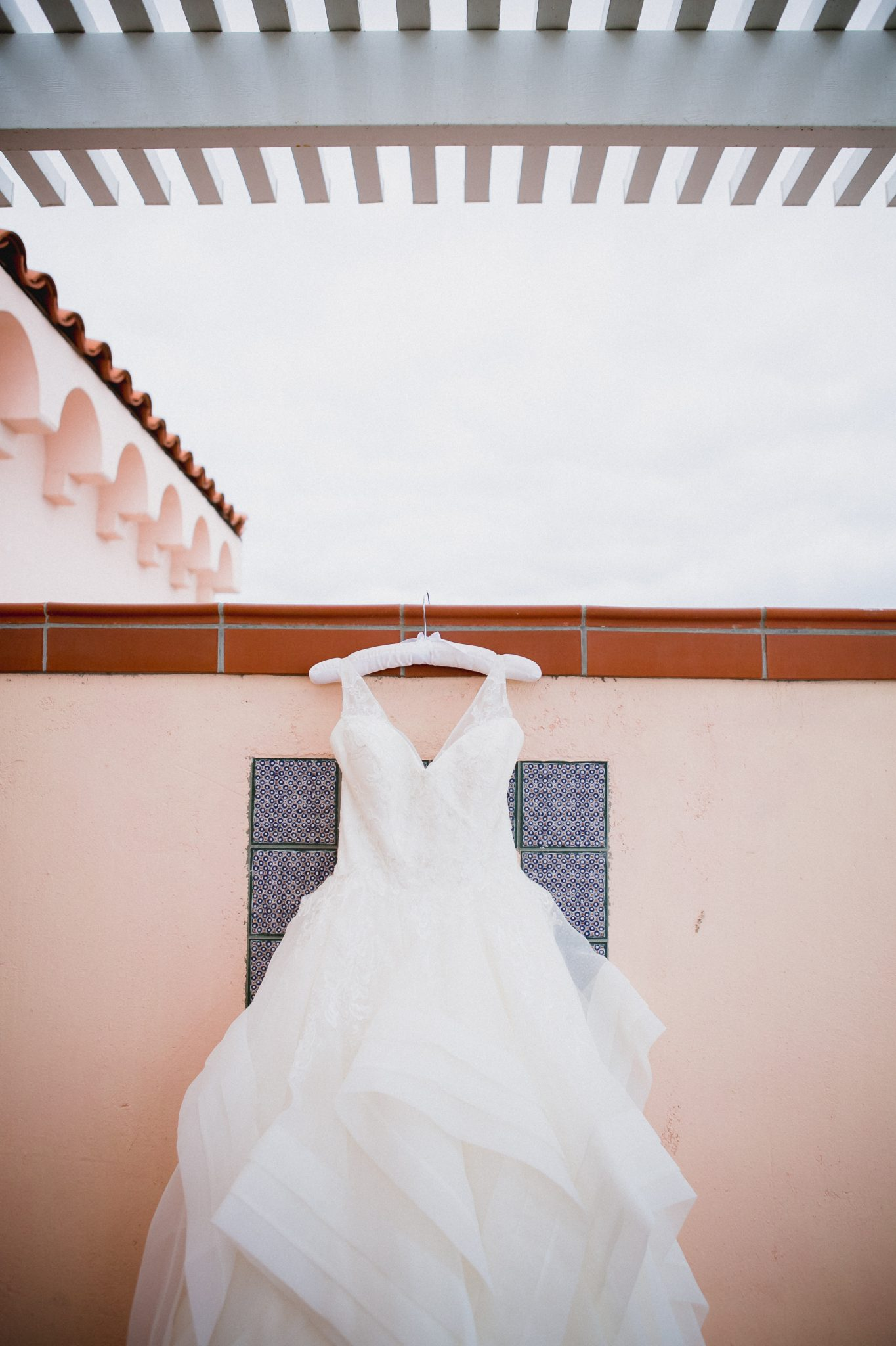 White lace and tulle wedding dress hanging up against stucco wall