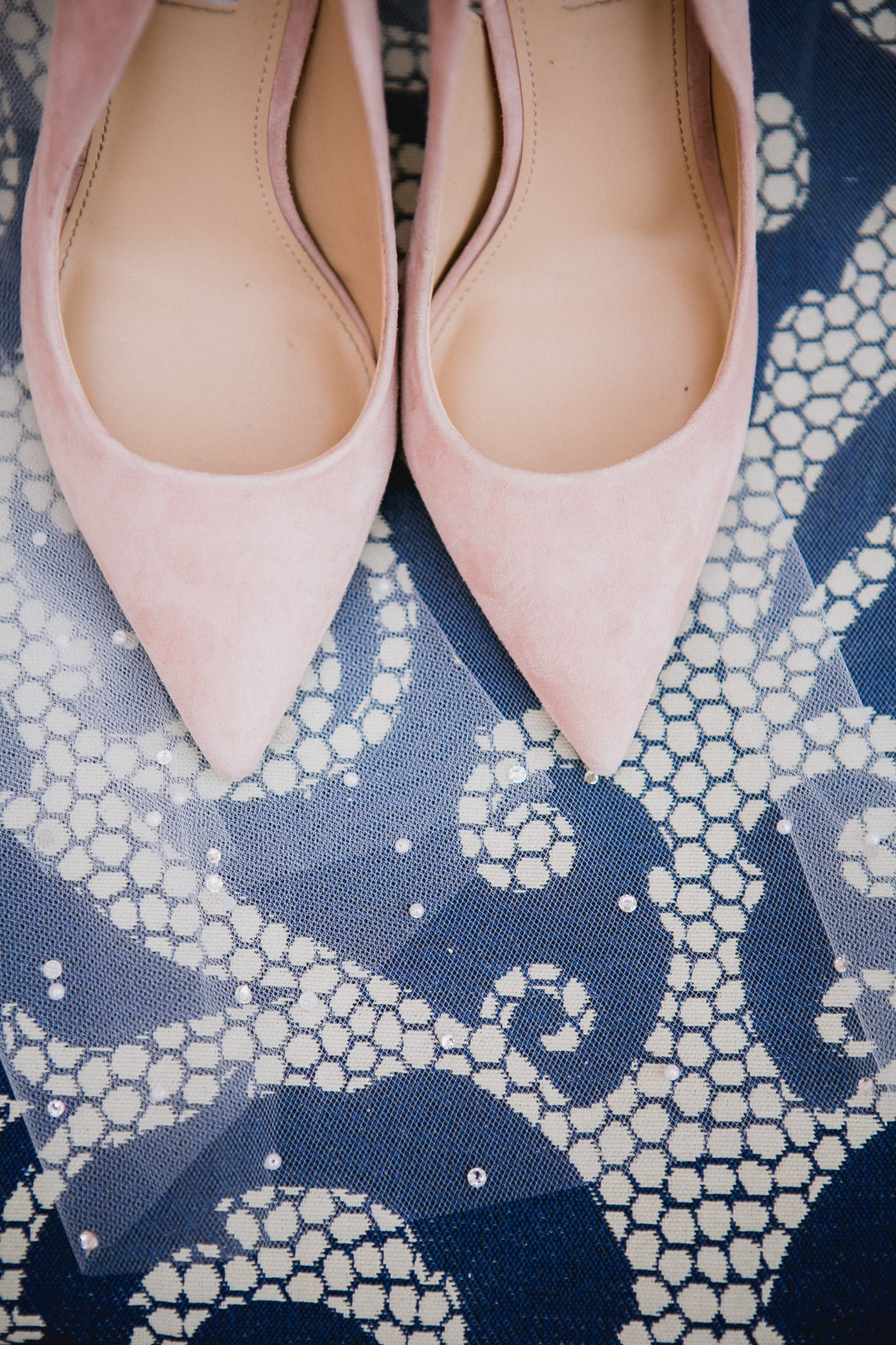 Blush pink heels with pointed toe sitting on a blue and white chair