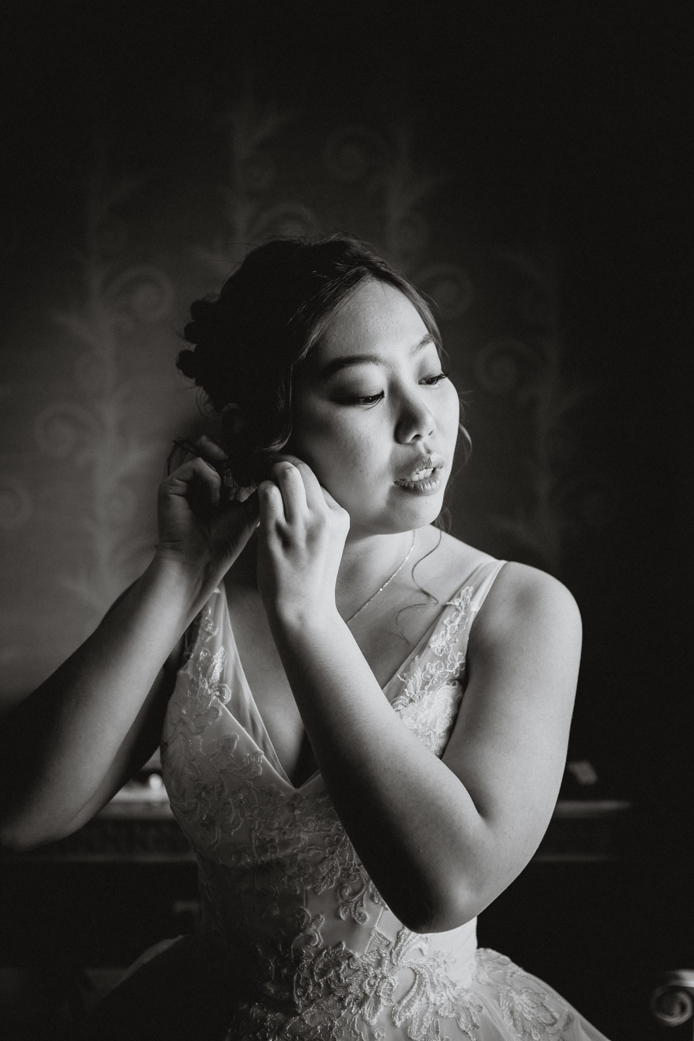 Black and white portrait of a bride putting her earrings on in a hotel room