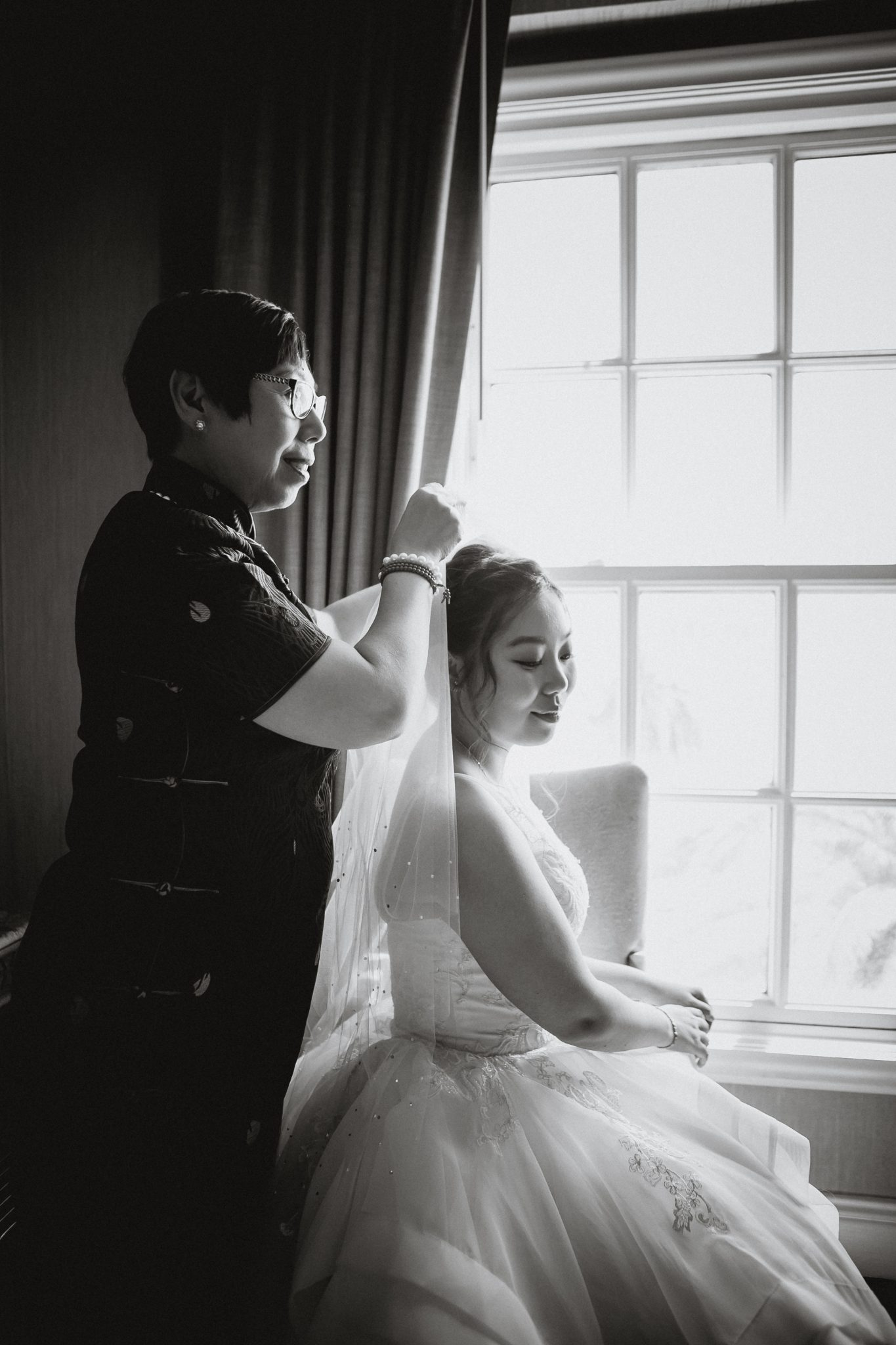 Mother of the bride placing the veil on the bride in the hotel suite