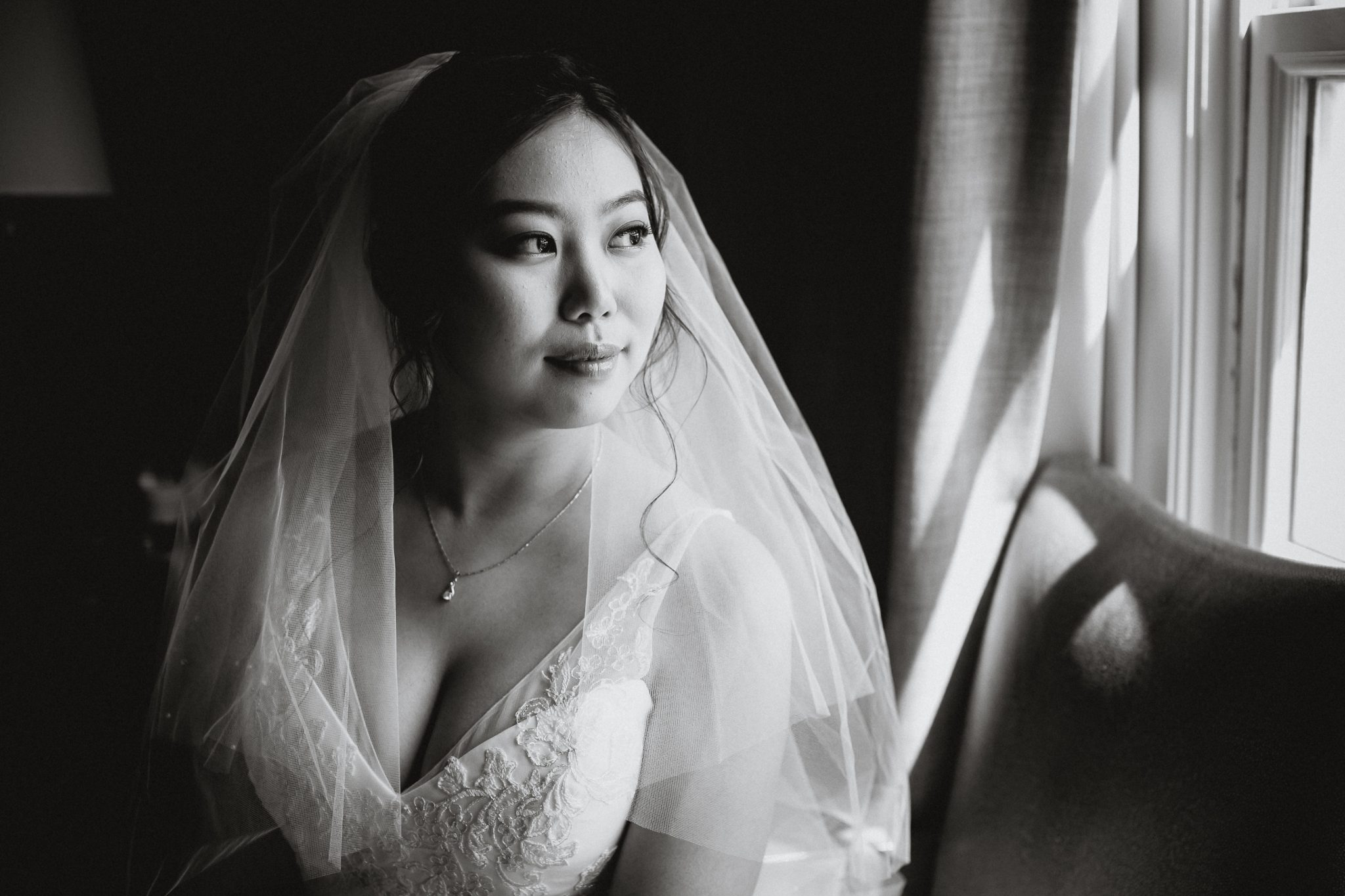 Black and white portrait of the bride smiling and looking out the window