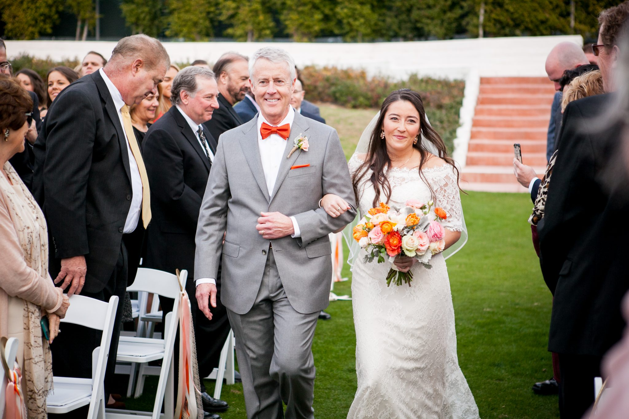 bride walks down the wedding ceremony aisle with her father