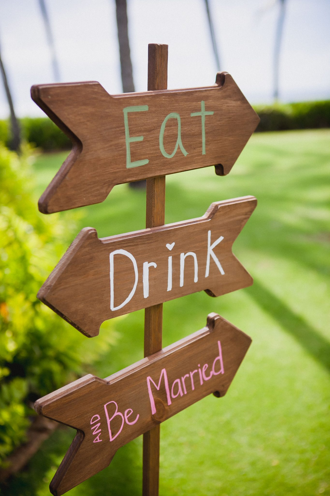 Wooden wedding arrow sign that says eat, drink, and be married