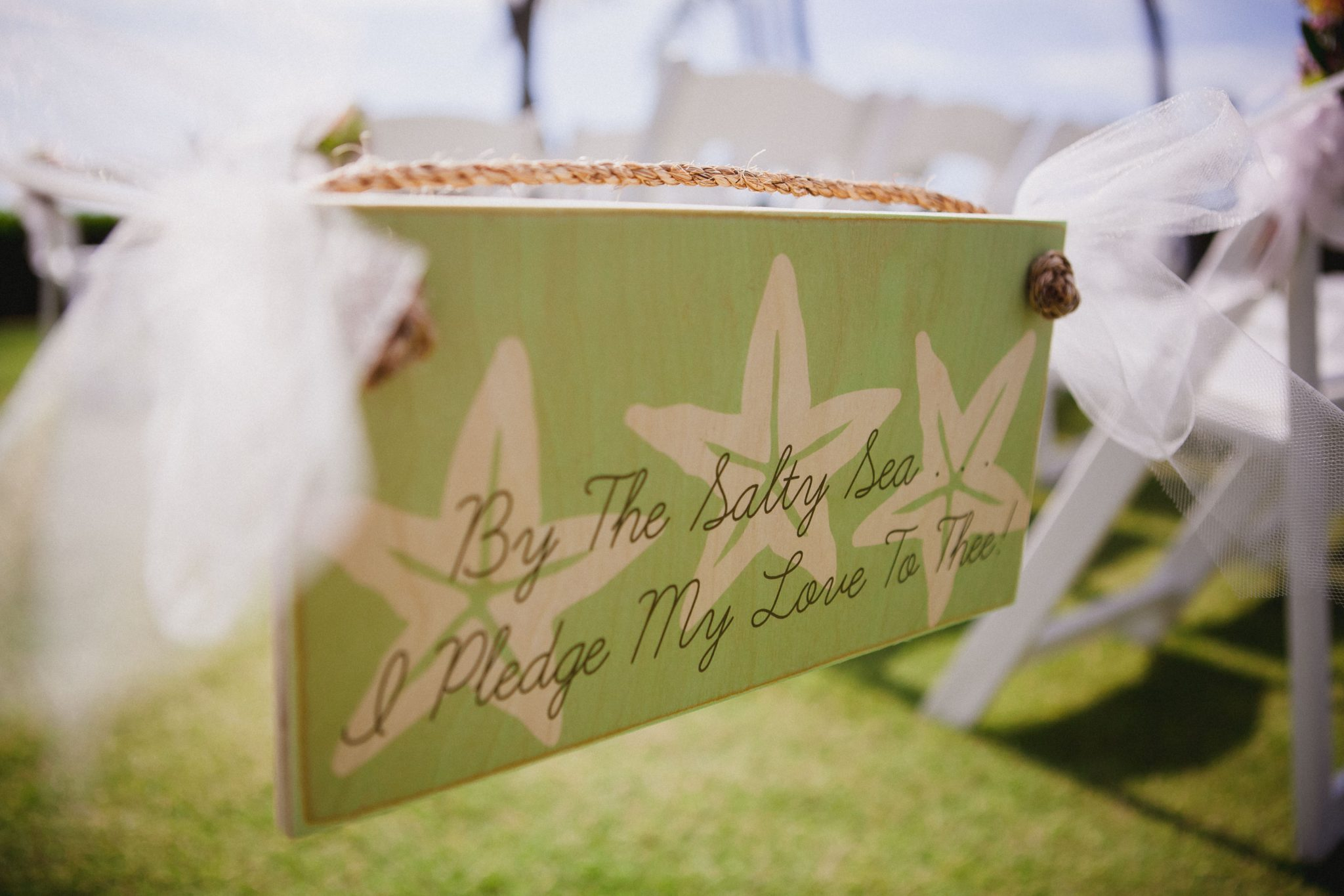 Wedding ceremony sign hanging in the middle of the aisle