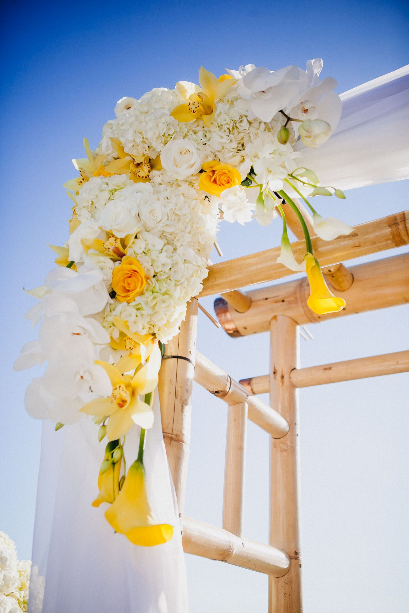 Ceremony wooden arbor detail shot showing yellow and white roses