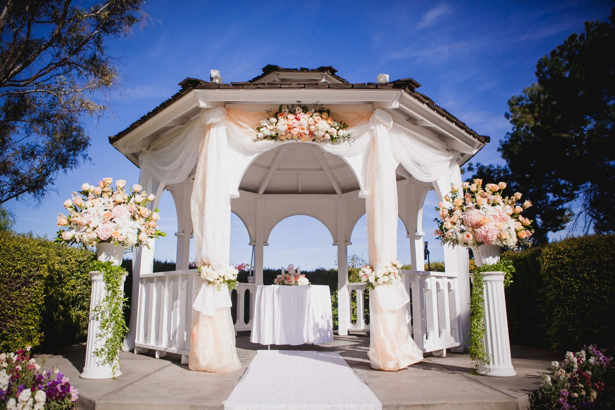 Outdoor wedding ceremony detail photo of the altar under a gazebo with white and pink roses