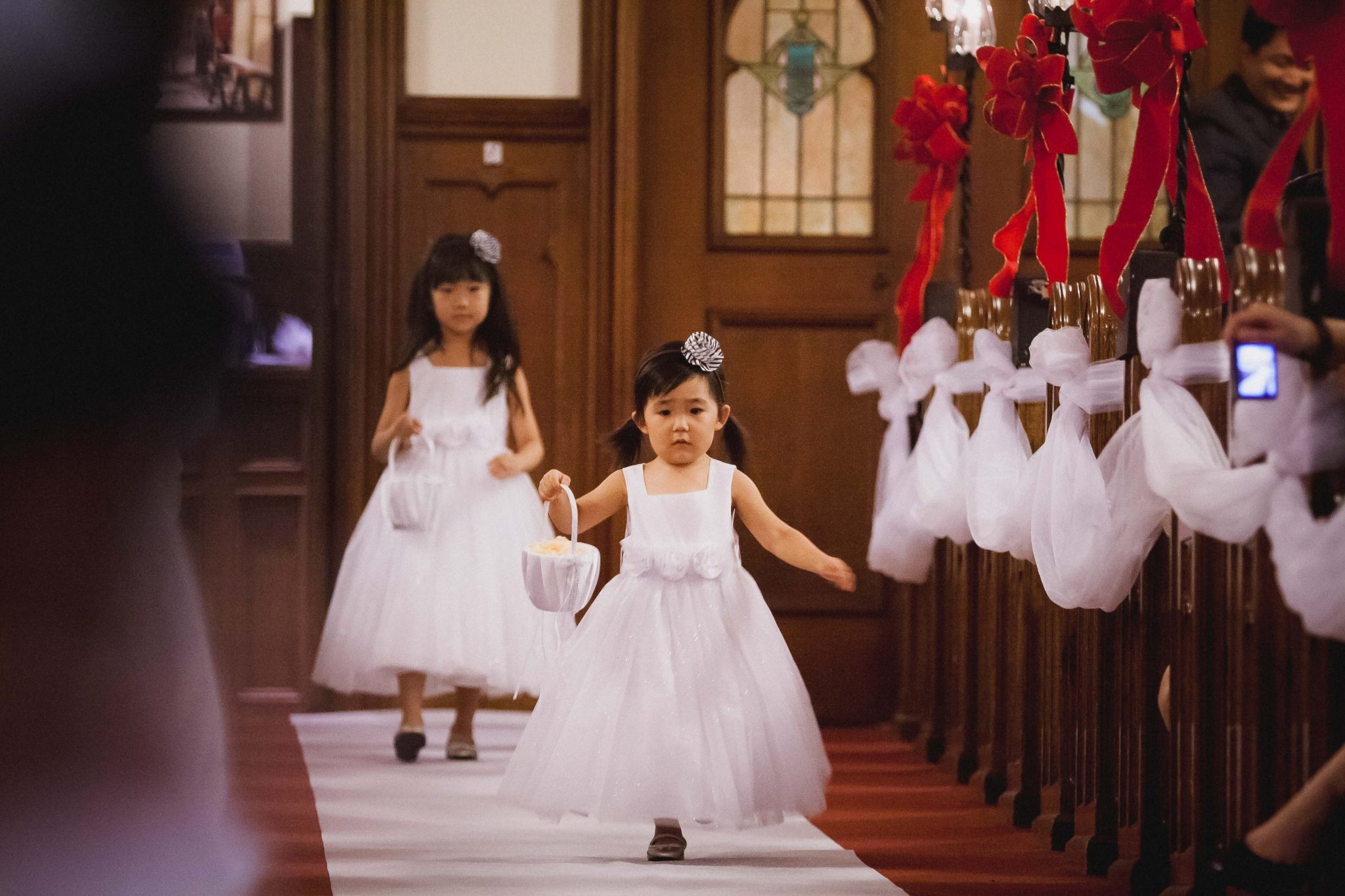 Flower girl running down the aisle during the wedding ceremony in San Diego