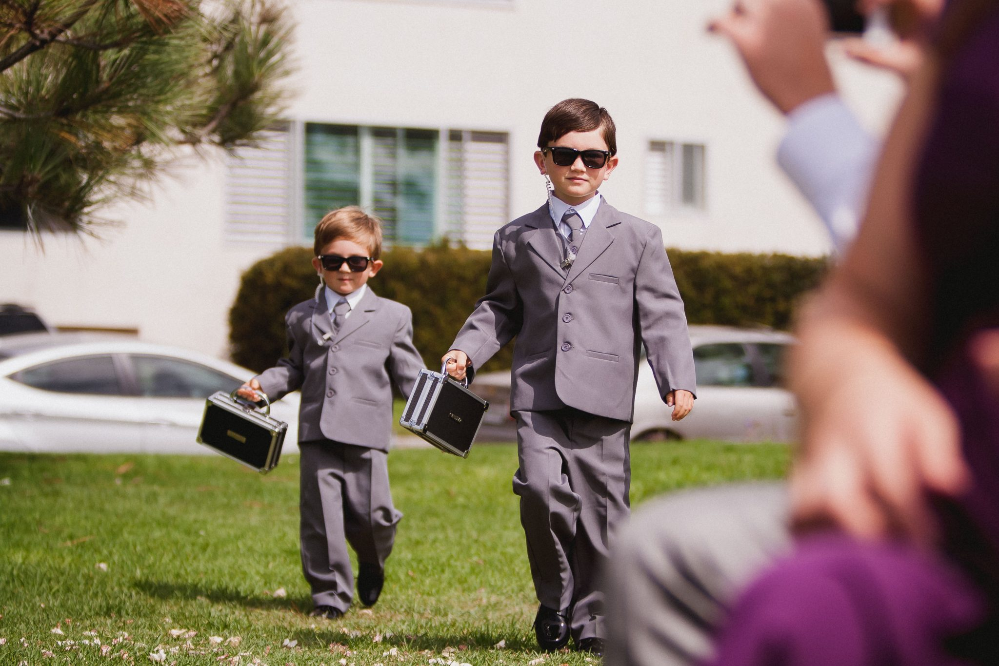 Two ring bearers dressed as security guards with the rings in mini briefcases