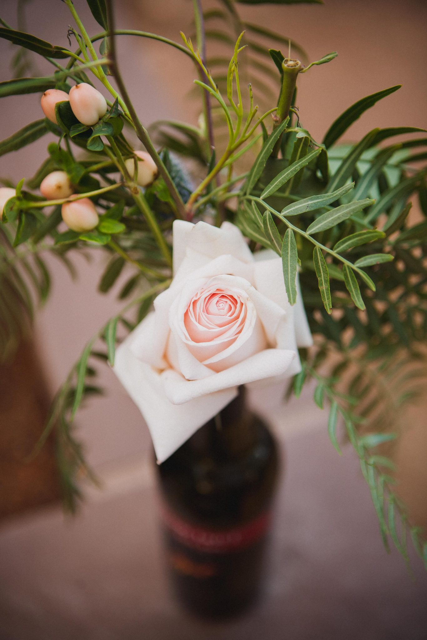 Light pink rose and green leaves in a beer bottle used as a wedding centerpiece