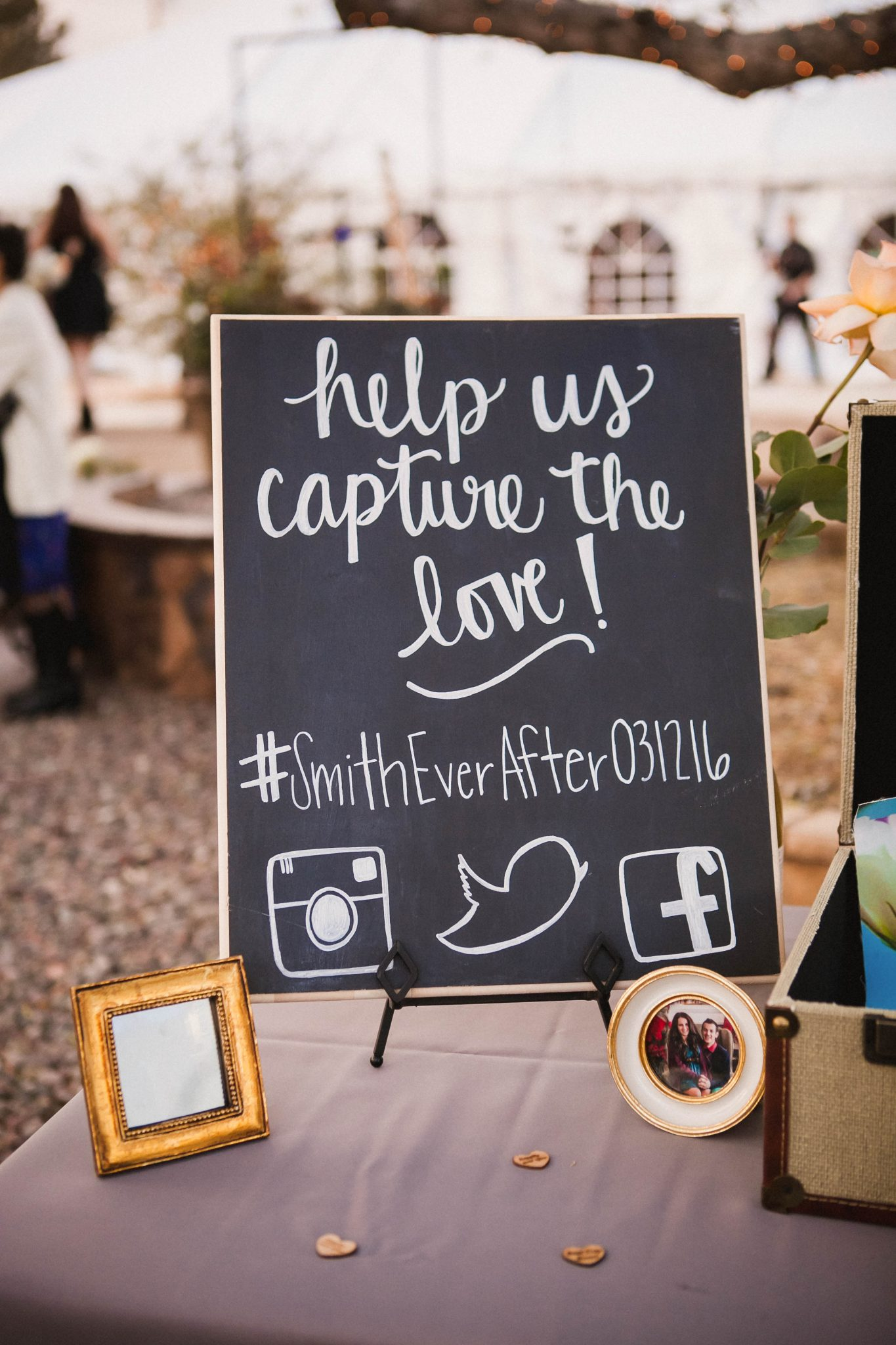 Wedding hashtag sign written on a chalkboard with white paint