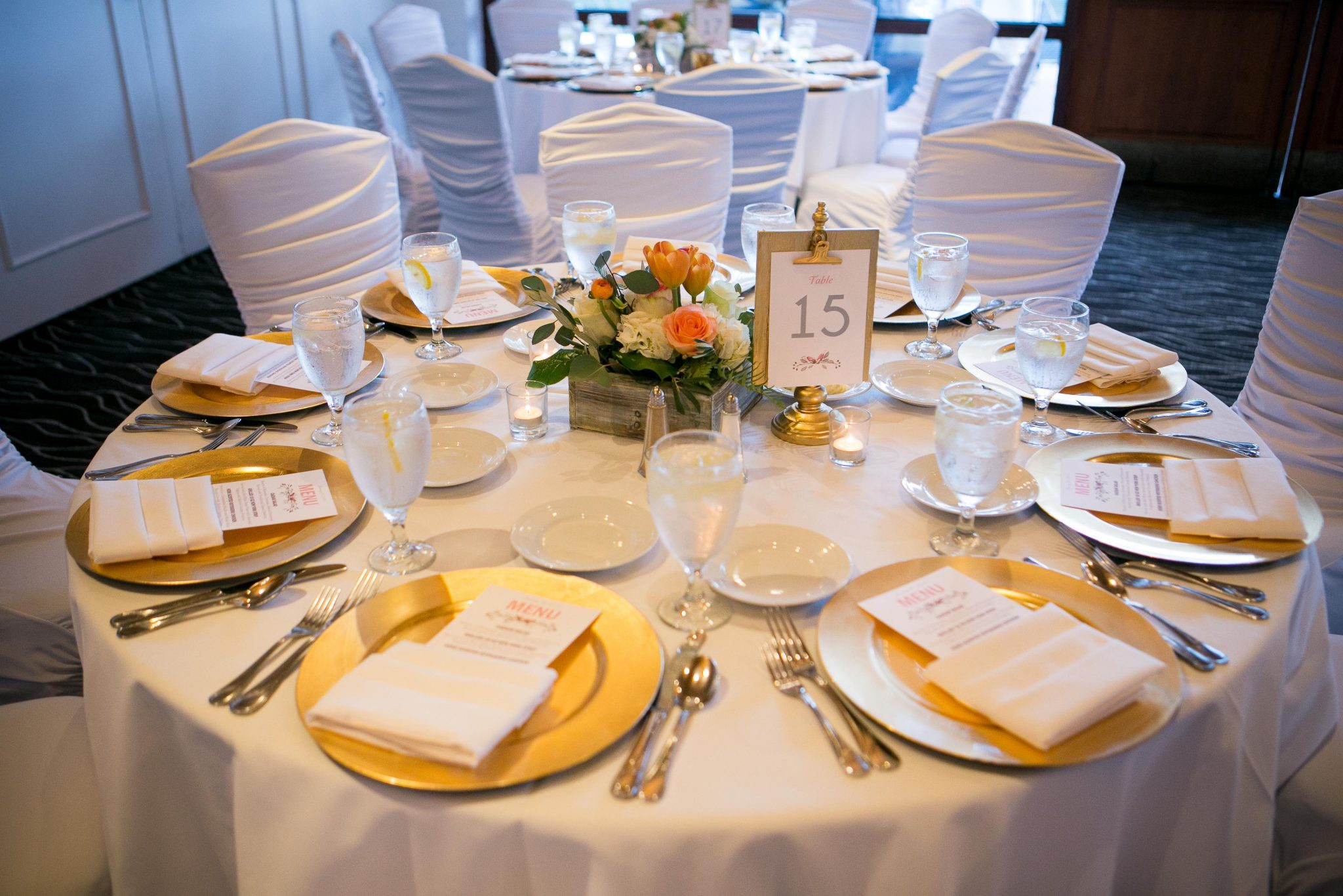 Wedding reception decorated tables with gold charger plates