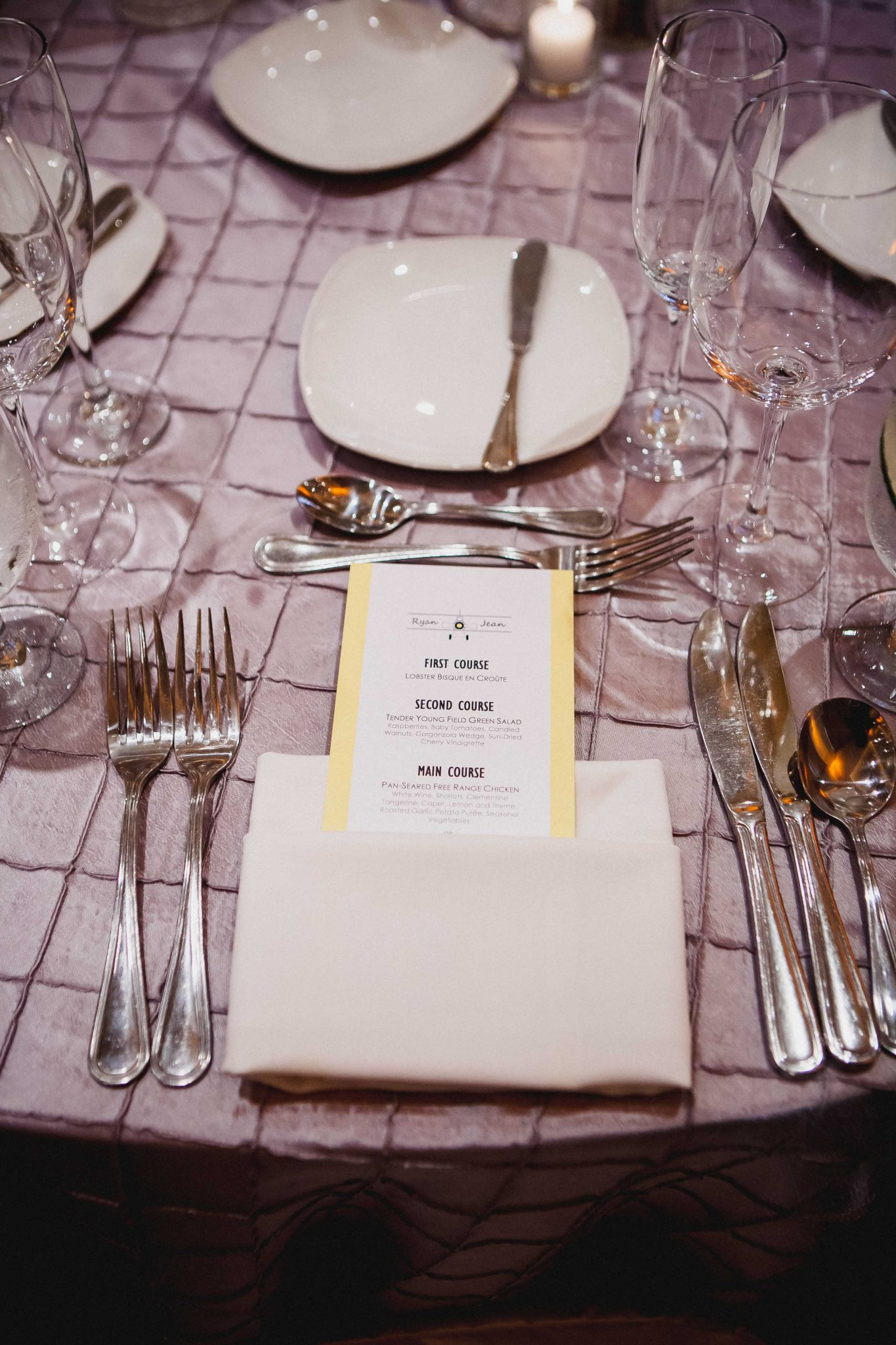 Wedding dinner menu placed inside of cloth napkin on a silver table cloth