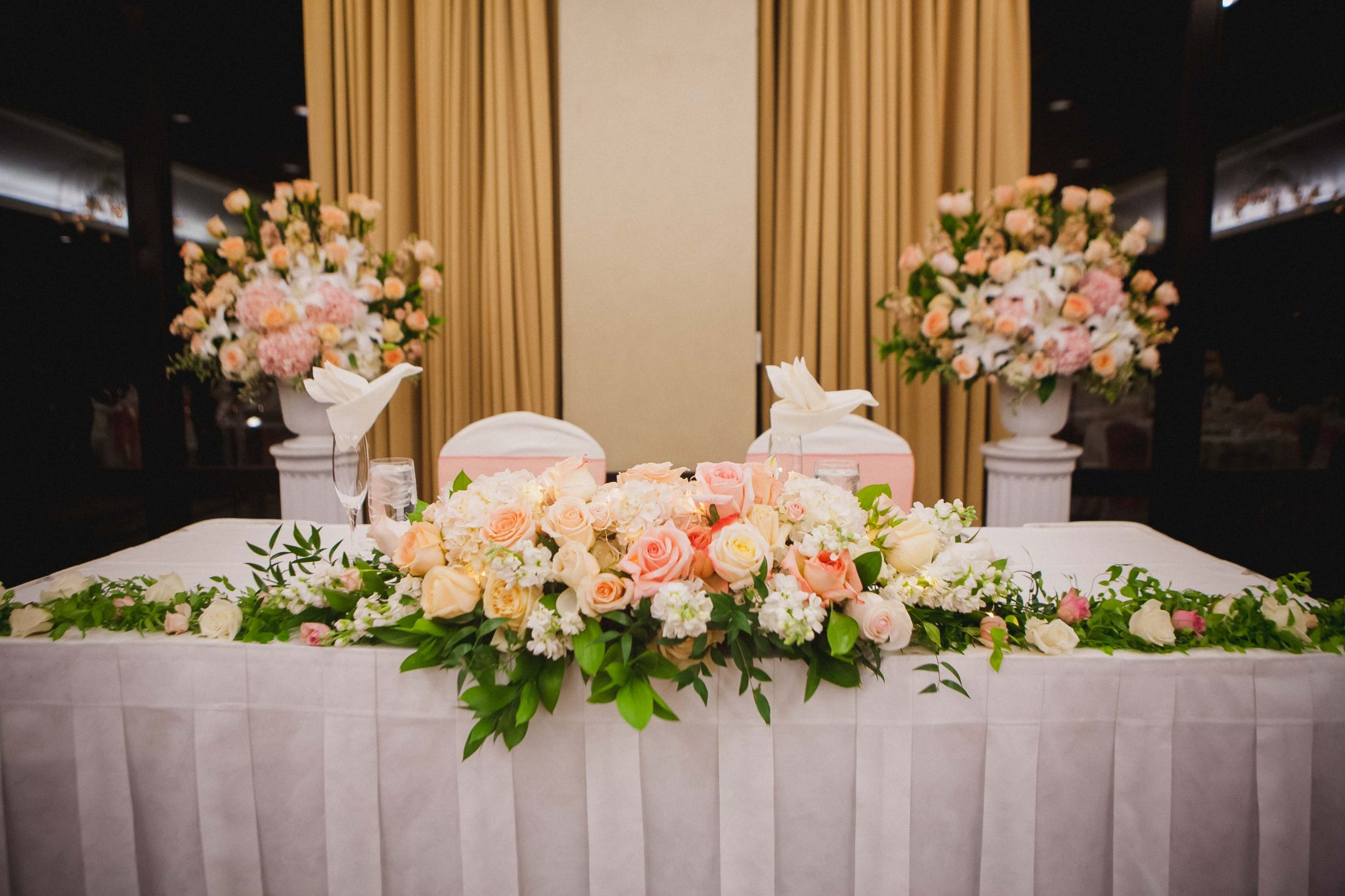 Wedding reception sweetheart table with pink and orange roses