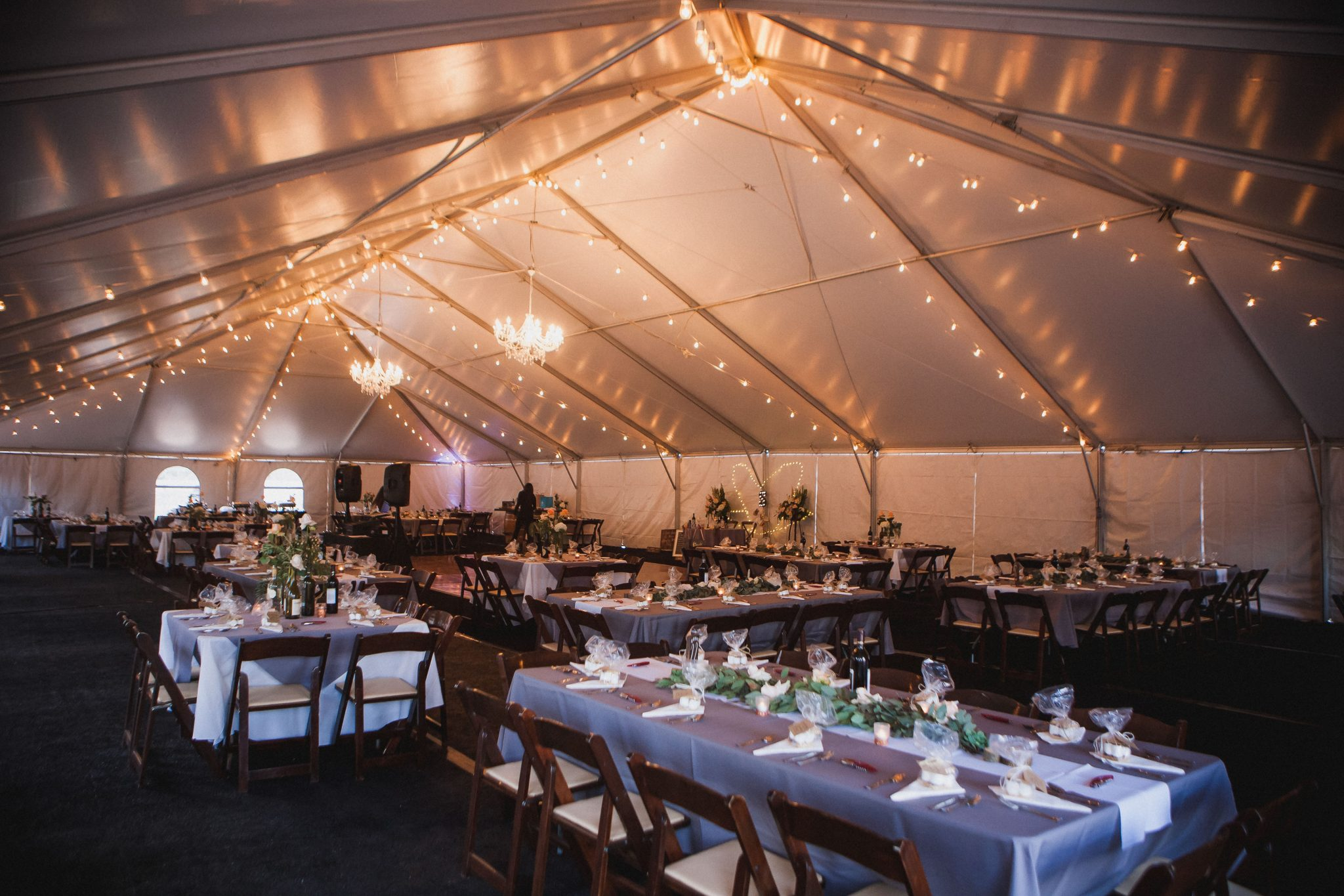 White tent reception with market string lights and chandeliers