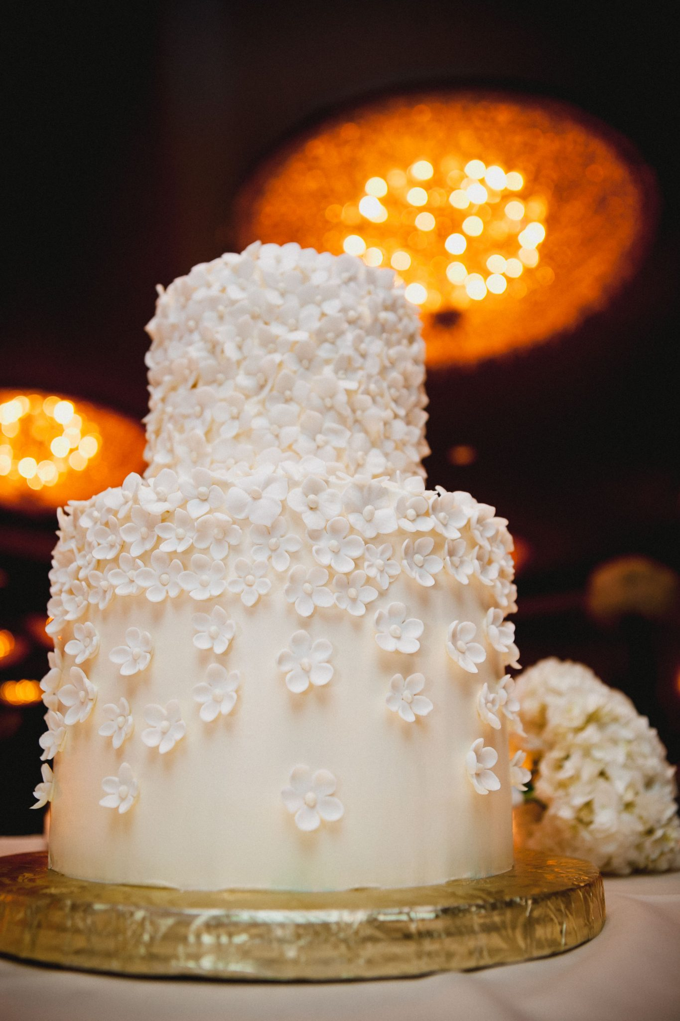 Thin gold cake stand with white flowers on the wedding cake