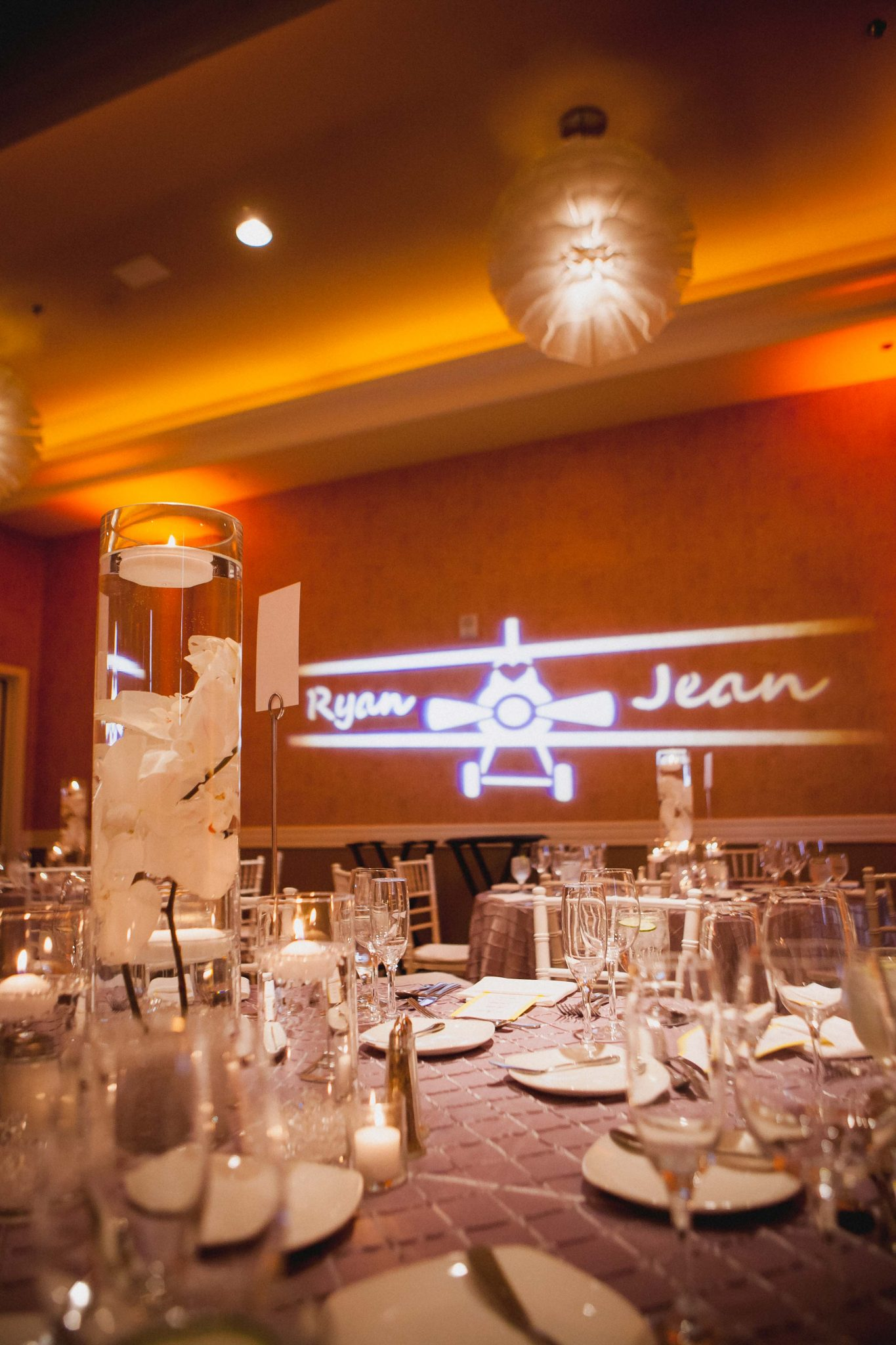Orange uplighting for wedding reception decor with a light projection on the wall