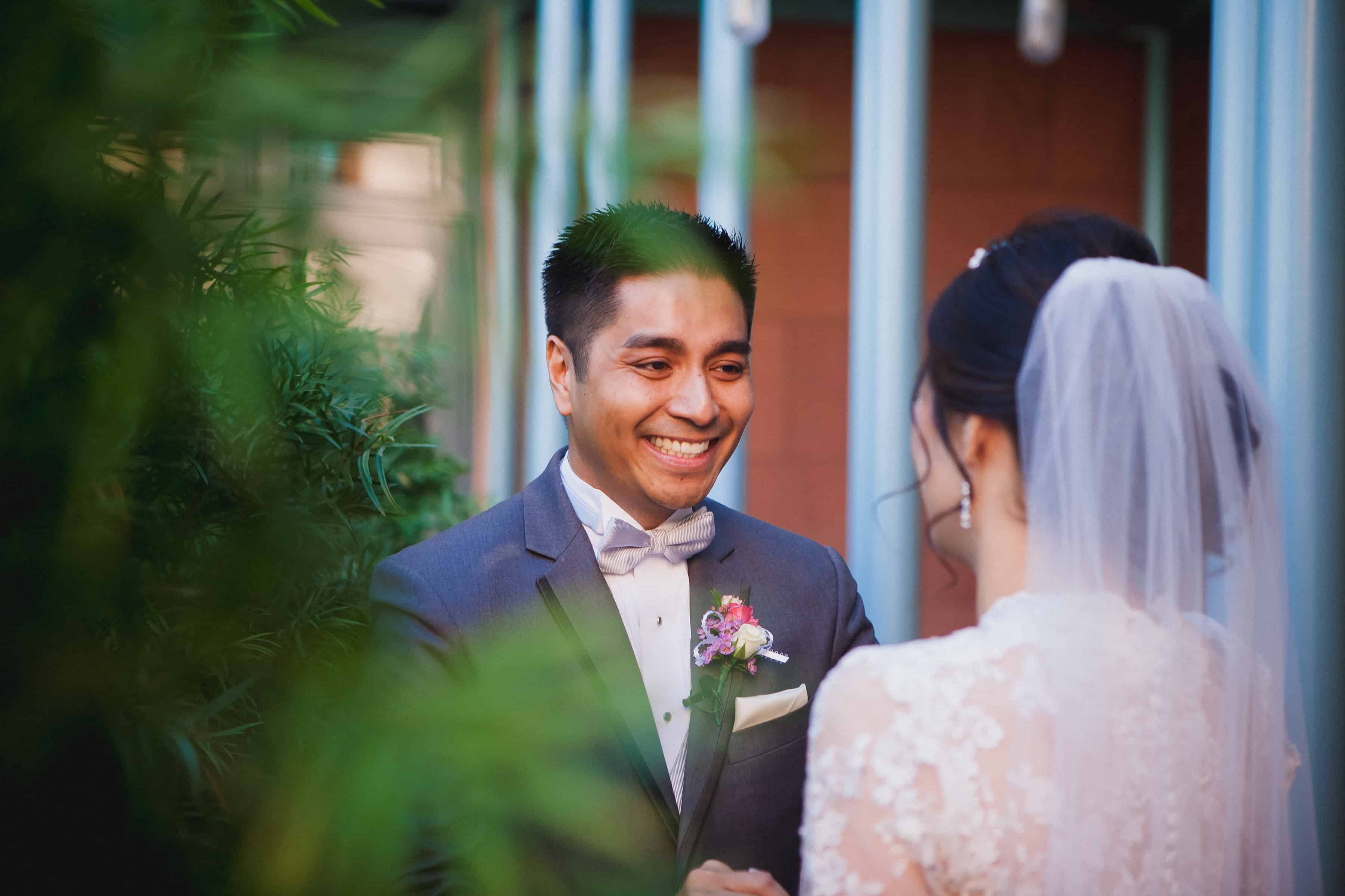 groom smiles as he turns around to see the bride for the first time during the wedding first look