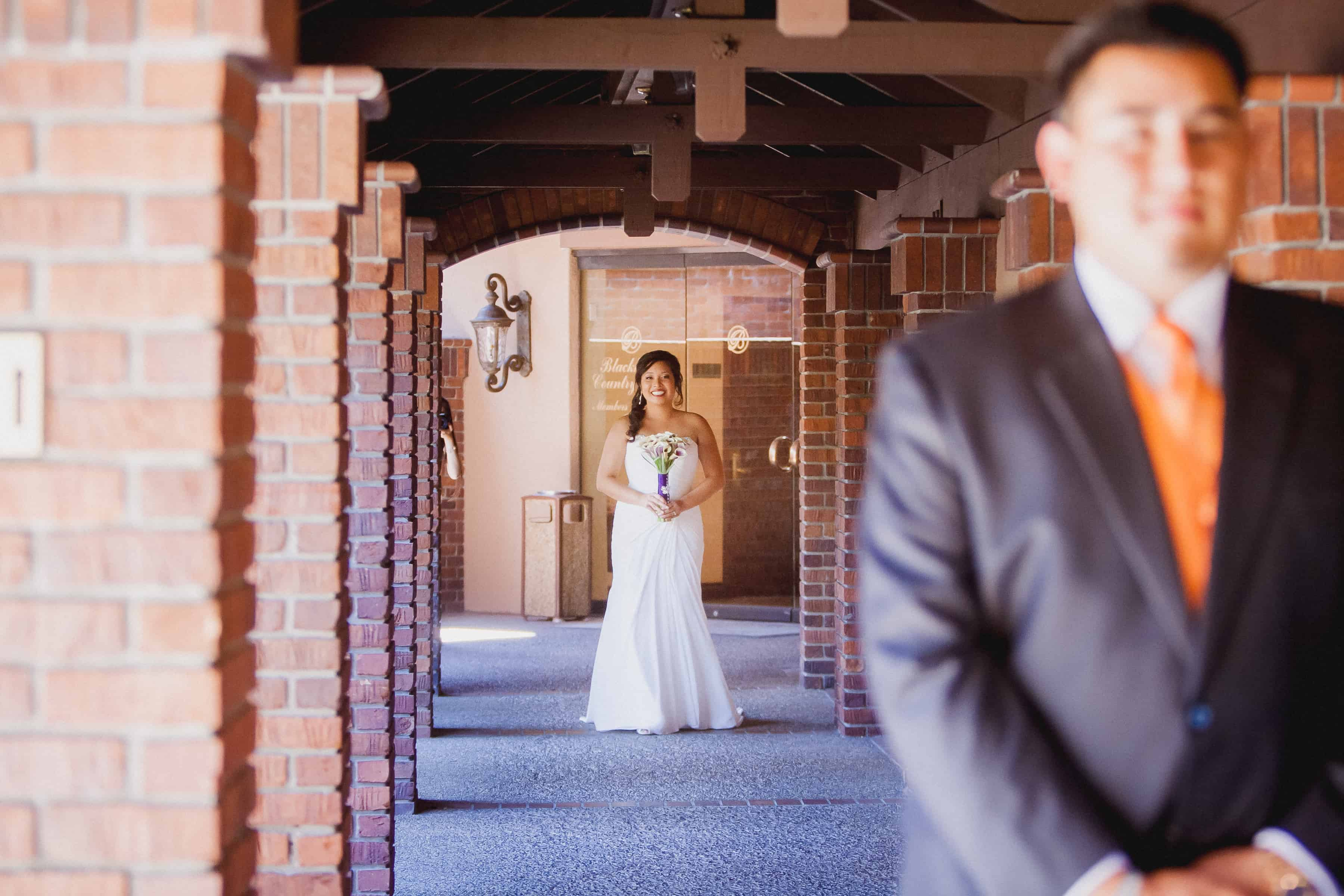 bride waits in anticipation to walk towards the groom during the first look
