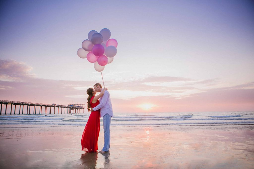 Couple kissing while holding balloons on the beach in La Jolla