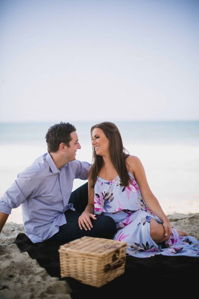 Having a picnic on the beach during their engagement shoot