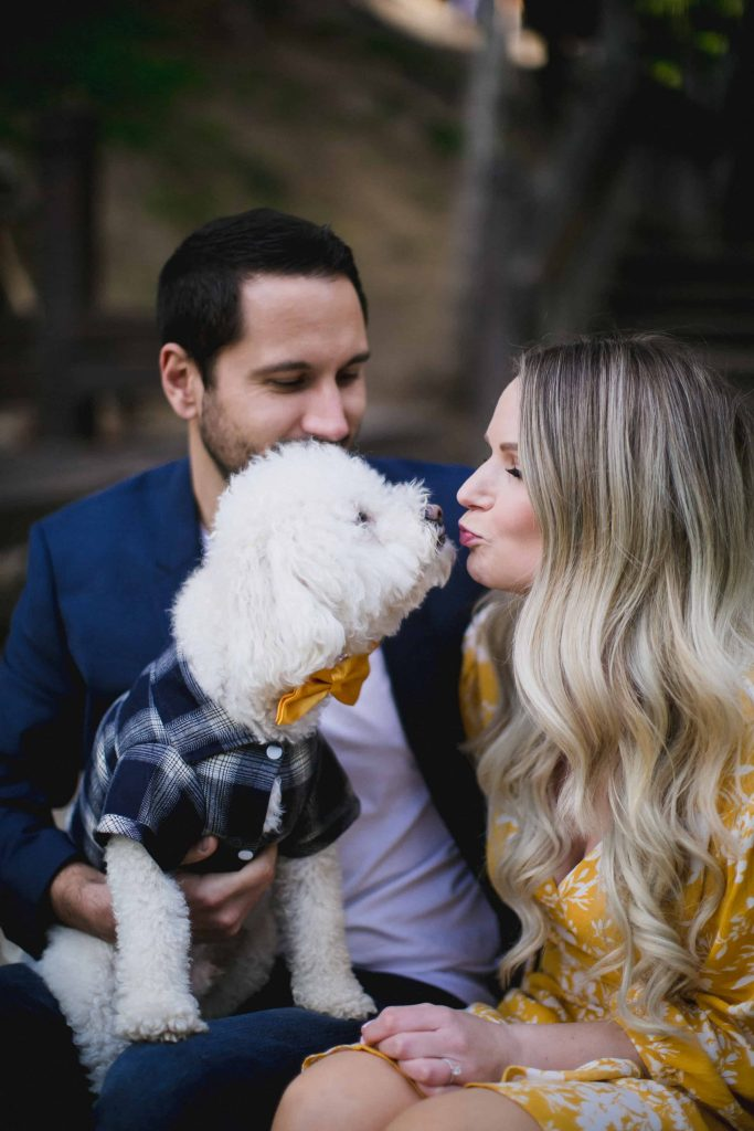 Woman kissing her dog during an engagement session