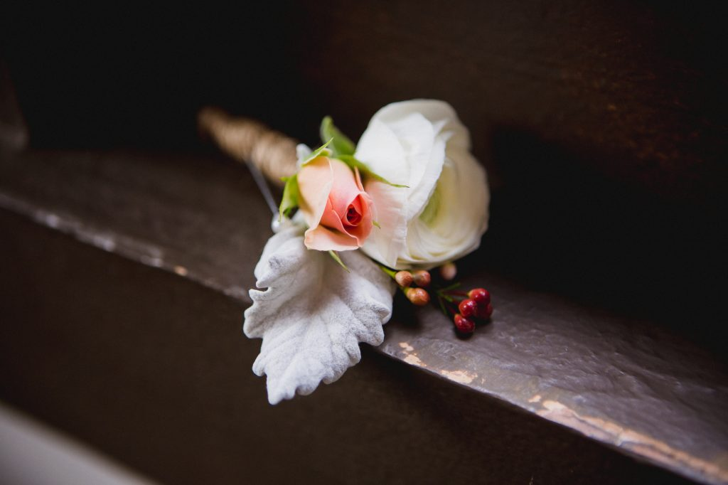 Groom's boutonniere with a white flower and small pink rose wrapped in burlap