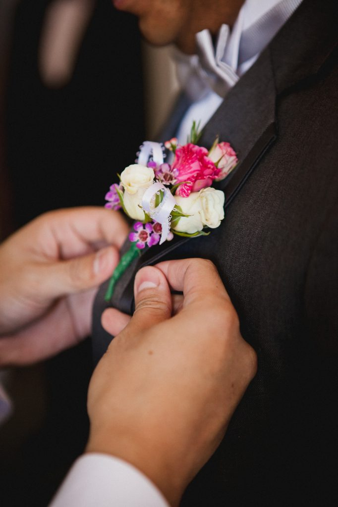Groomsman pinning a white and pink flower boutonniere onto the groom's jacket