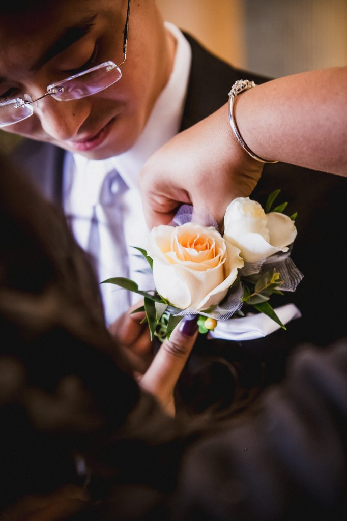 Woman pinning an orange rose boutonniere on the groom's lapel on the wedding day