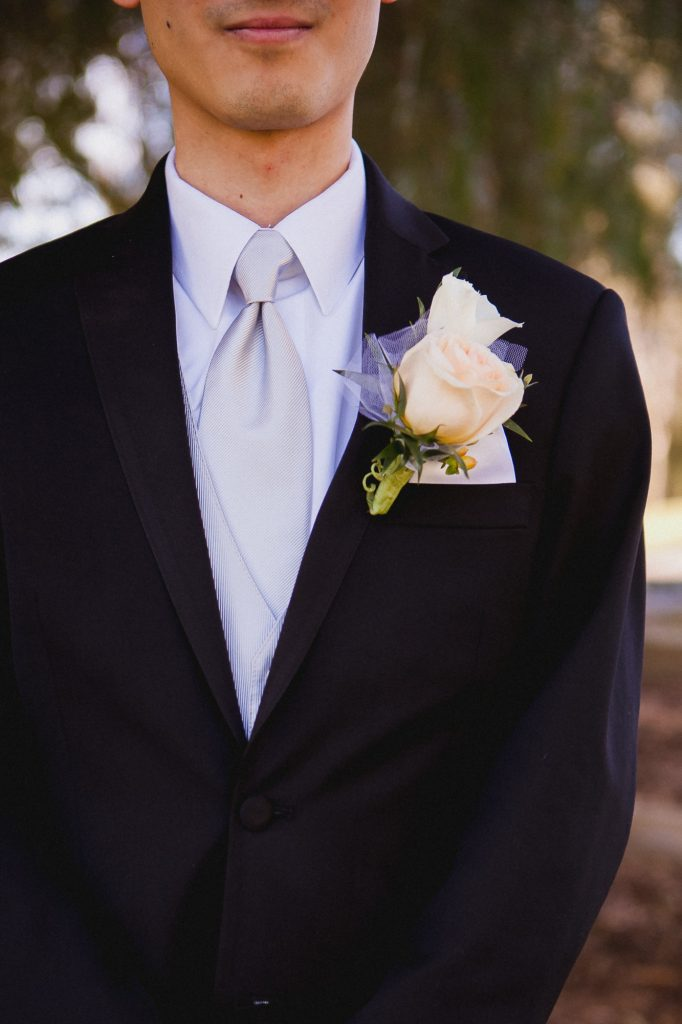Detail photo of the groom's rose boutonniere and light gray tie