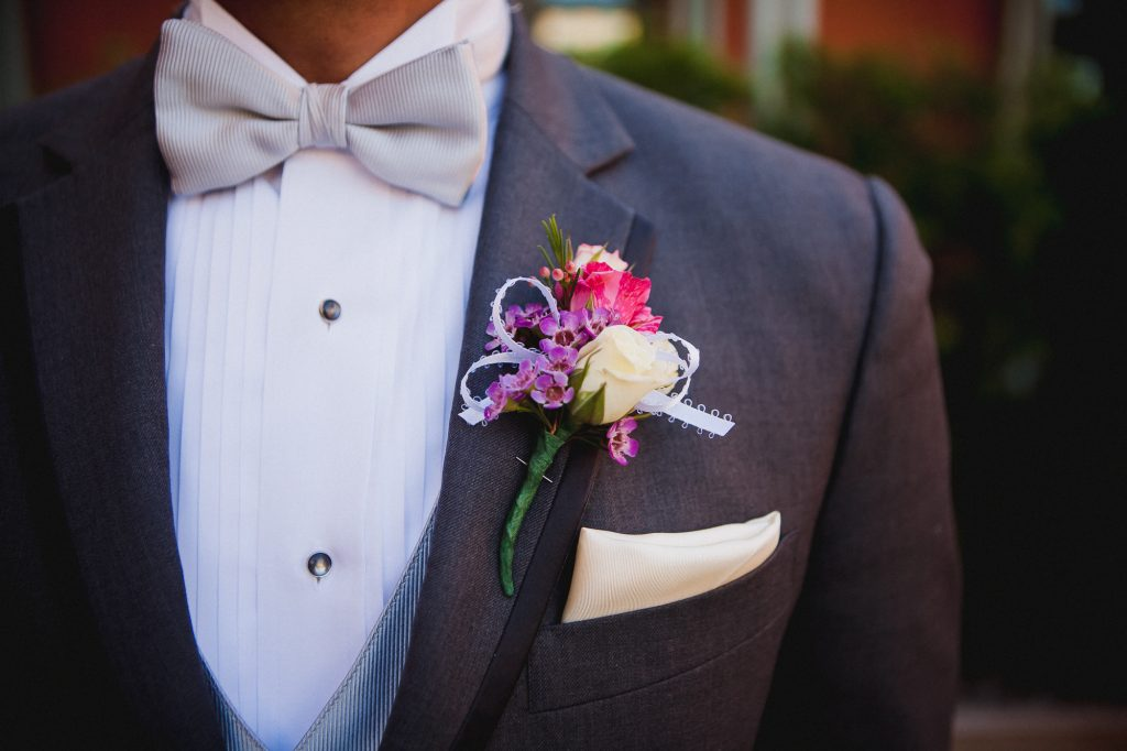 Decorative boutonniere with small purple flowers and a white rose for the groom