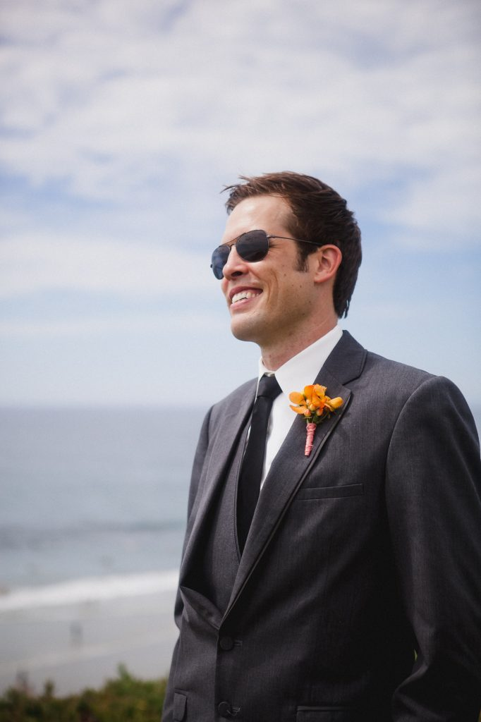 Groom by the ocean wearing a gray suit with a light orange boutonniere