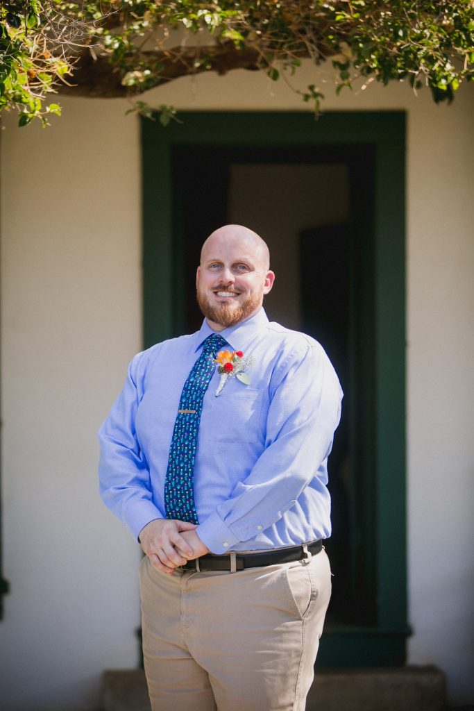 Groom portrait wearing a blue dress shirt with khaki pants for an afternoon wedding